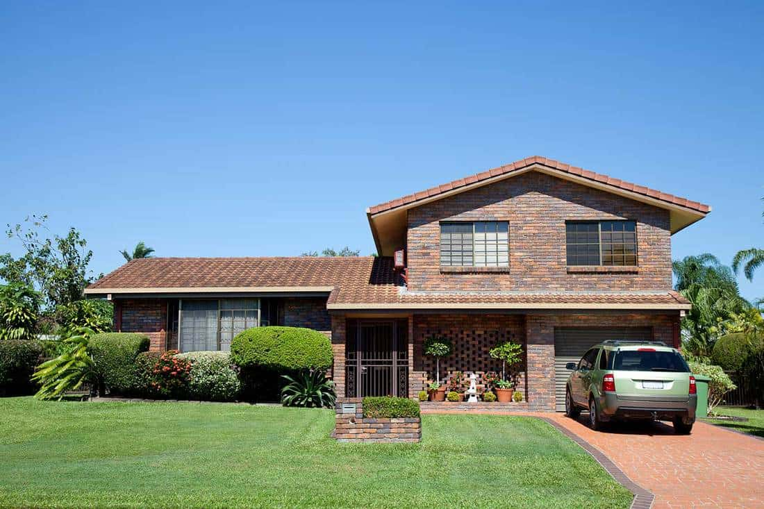Front view of a tidy split level brown brick family home with green grass and blue sky and car in driveway