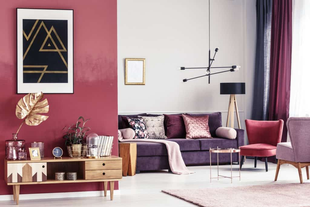 Gold leaf on wooden cupboard against red wall with black poster in spacious living room interior