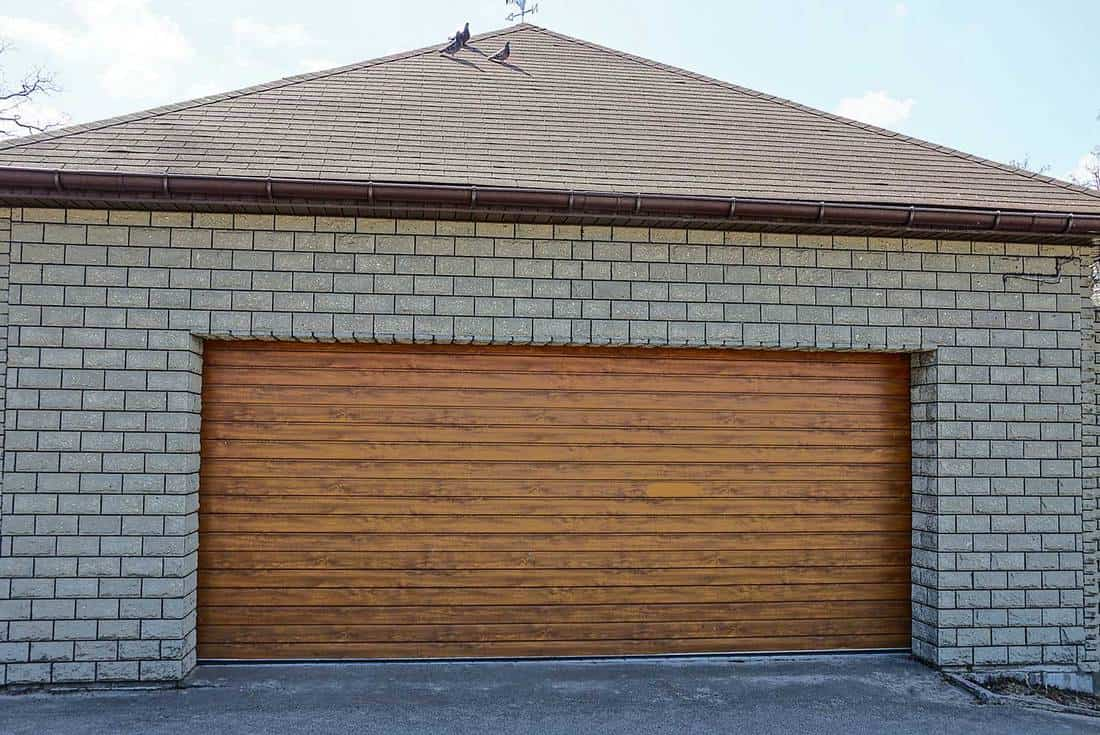 Gray brick garage with brown gates on the street