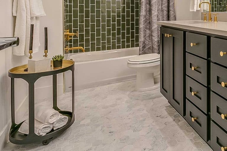 Green theme beautiful bathroom with brass faucets and fixtures, Bathroom Floor Not Level - What To Do?