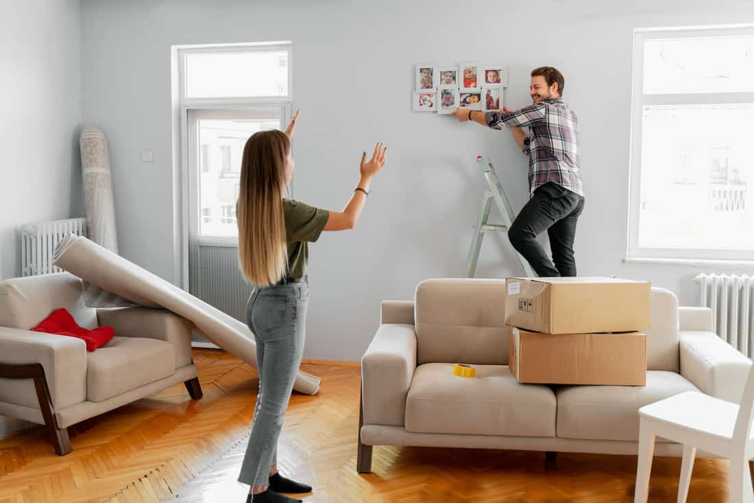 His wife shows him helping while the man is posting photos in their newly moved house