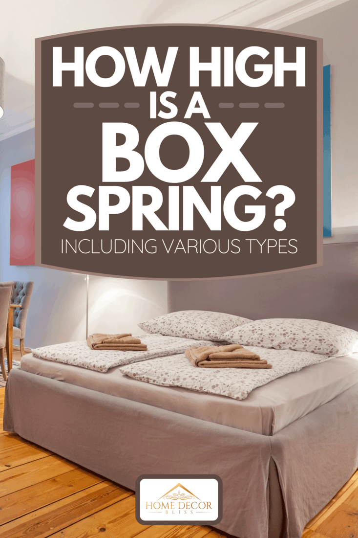 A box spring bed with a king sized mattress, blankets and pillows as well as bedside lamp, How High Is A Box Spring? [Including Various Types]