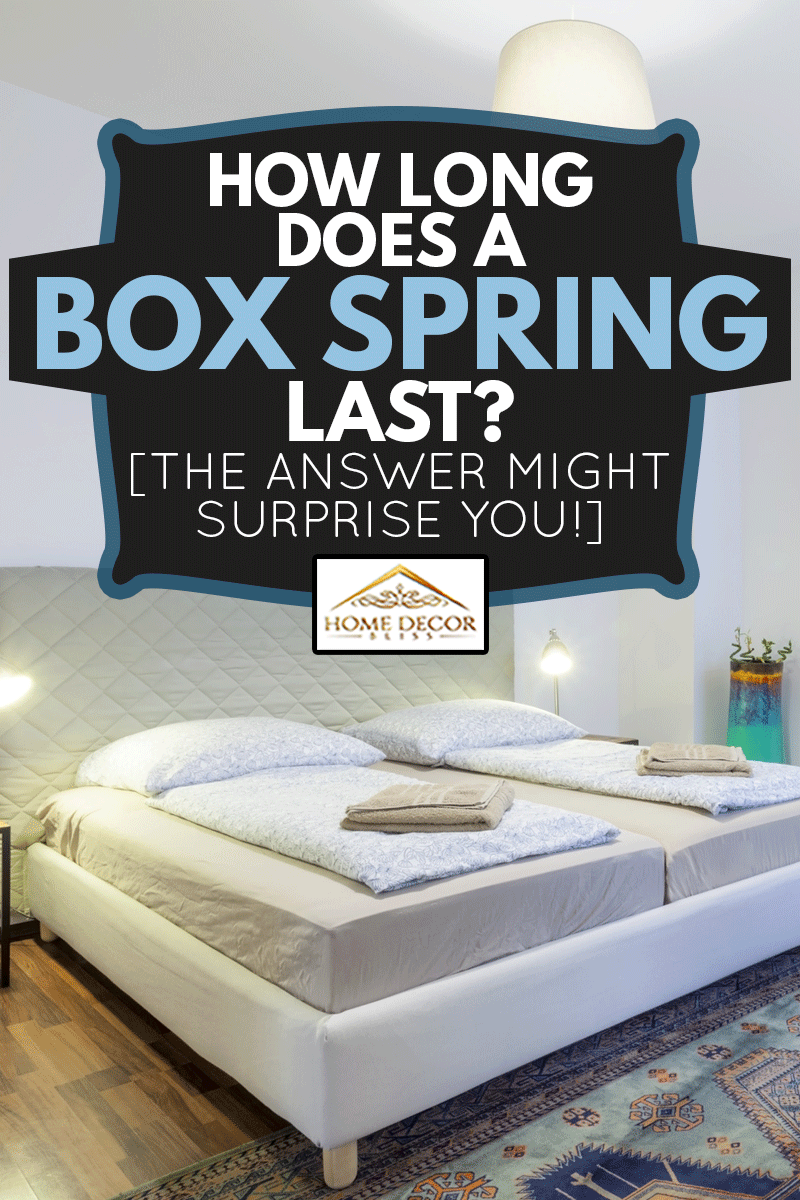 Very modern and elegant bedroom with a King sized bed, carpet, bedside tables, a large wall mirro and armchair., How Long Does A Box Spring Last? [The Answer Might Surprise You!]