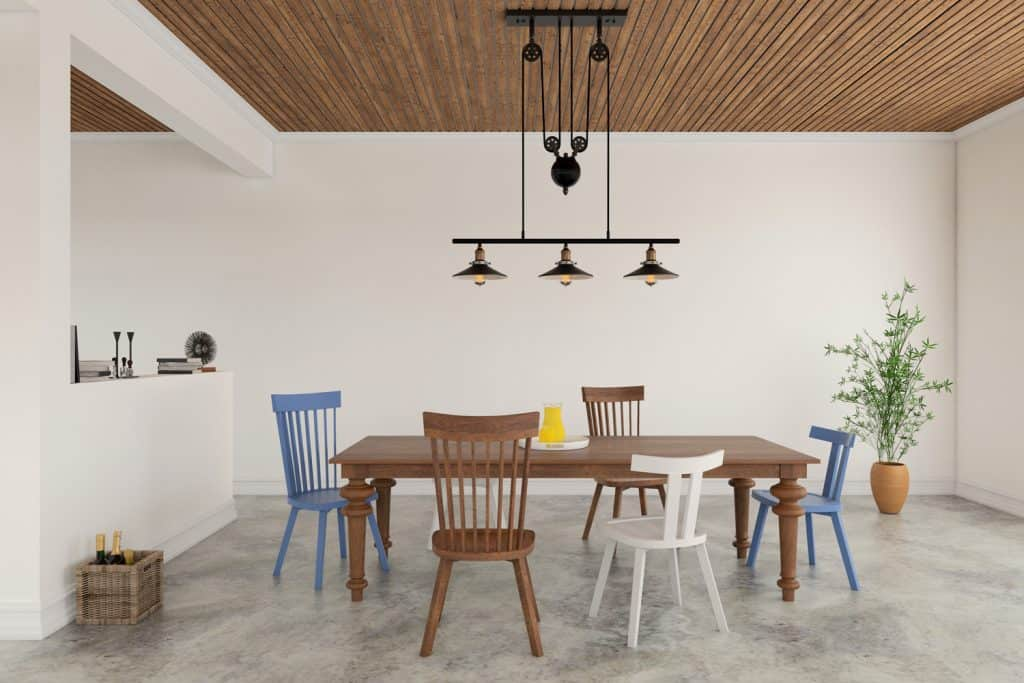Interior is white with concrete polished floor and wooden ceiling. Ornate vintage chandelier over the table.