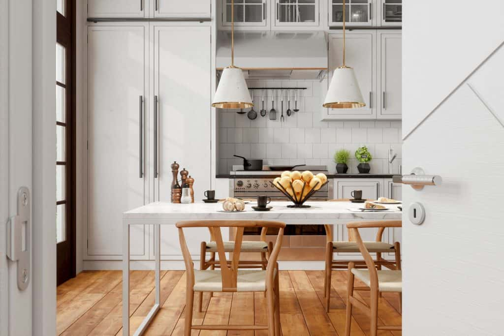 Interior of a Scandinavian themed kitchen with wooden chairs, wooden flooring, and white backsplash on the countertop area