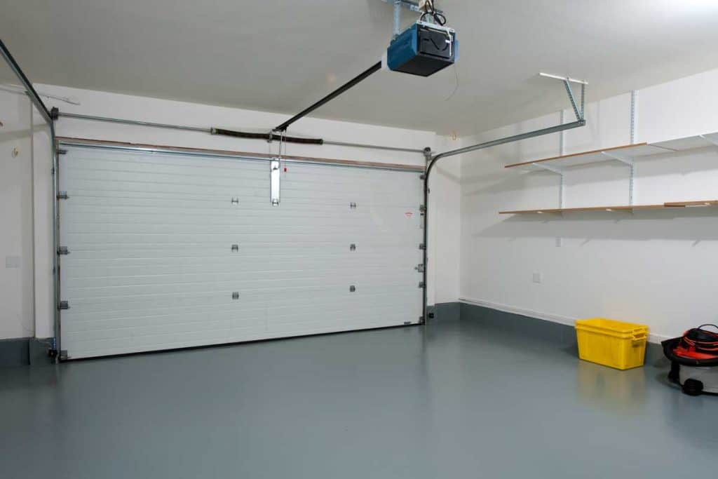 Interior of a clean garage in a house with white walls and gray floor, Should Garage Walls Be Textured?
