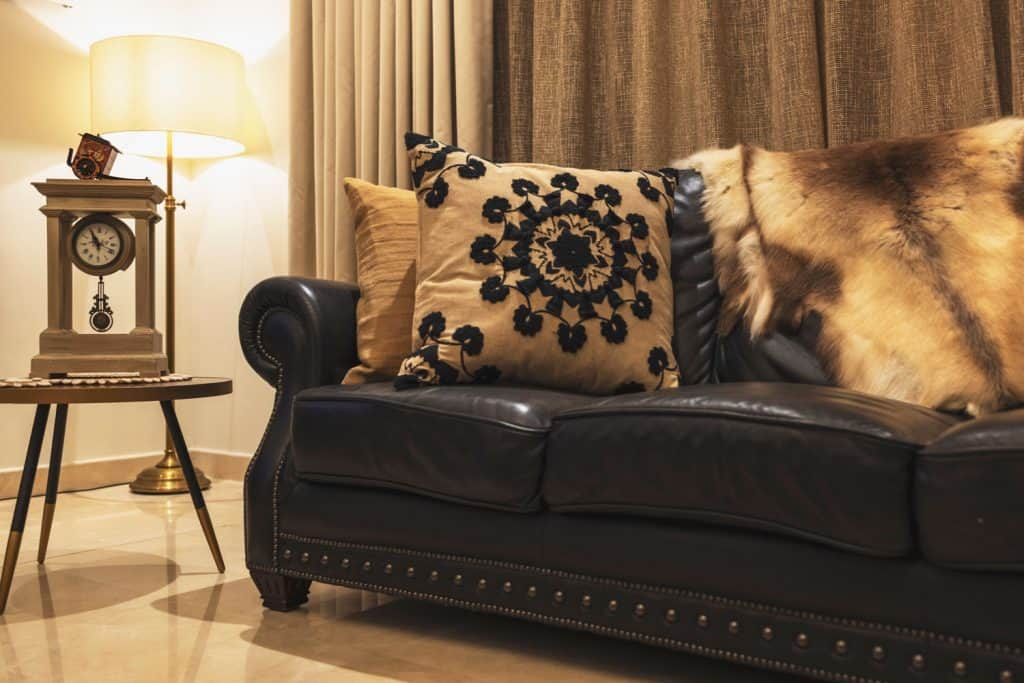 Interior of a comfortable living room with a black leather sofa and patterned throw pillows