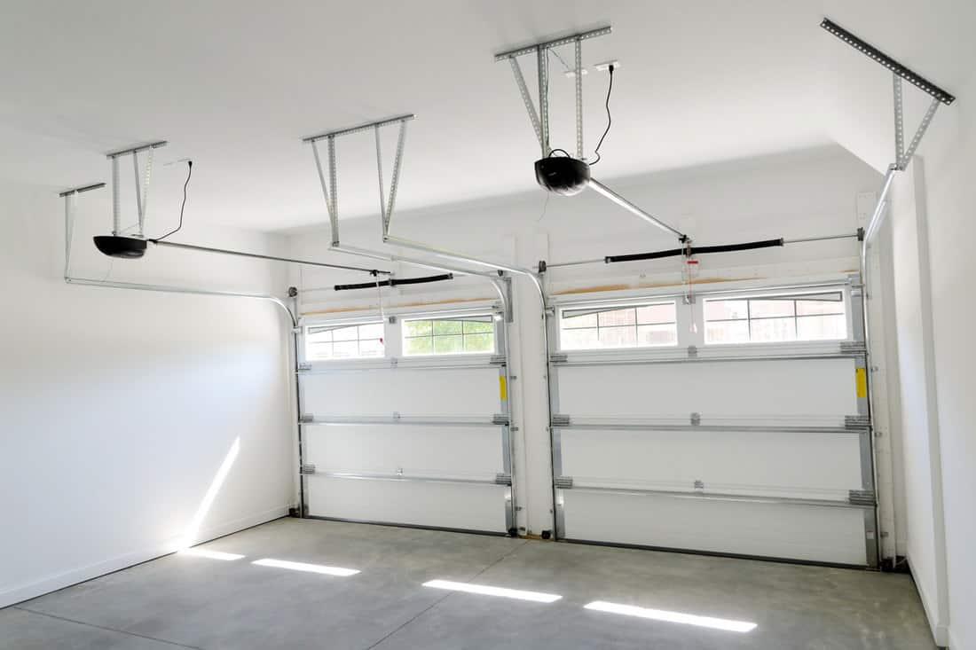 Interior of a garage with two garage door openers, 5 Types Of Garage Door Openers [Plus Some Need To Know Info]
