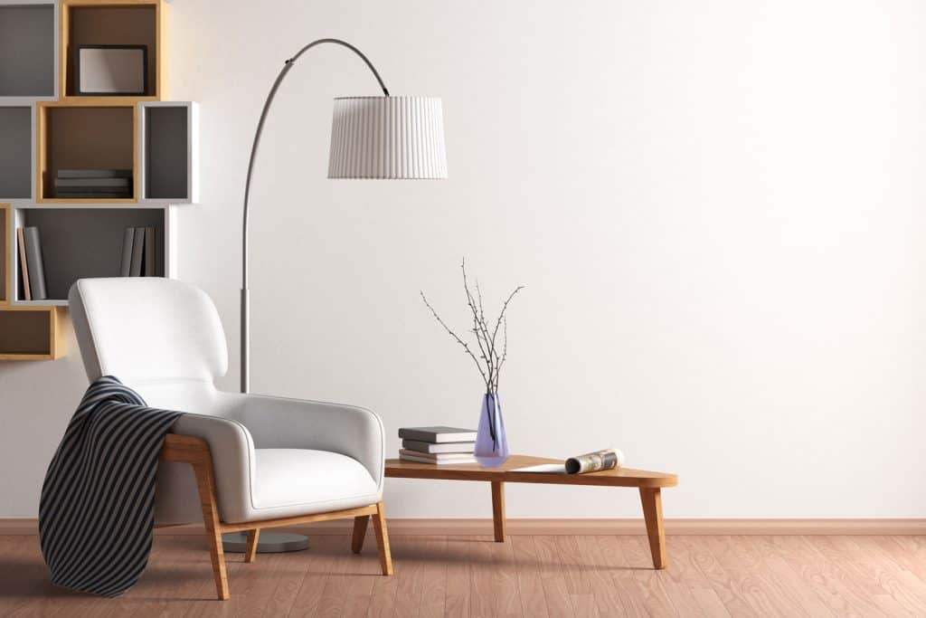interior of a gorgeous modern living room with a modern designed divider and a white painted wall with a tall arched floor lamp