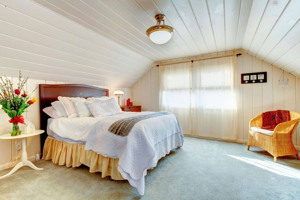 Interior of a mansard bedroom with wooden ceilings and sidings