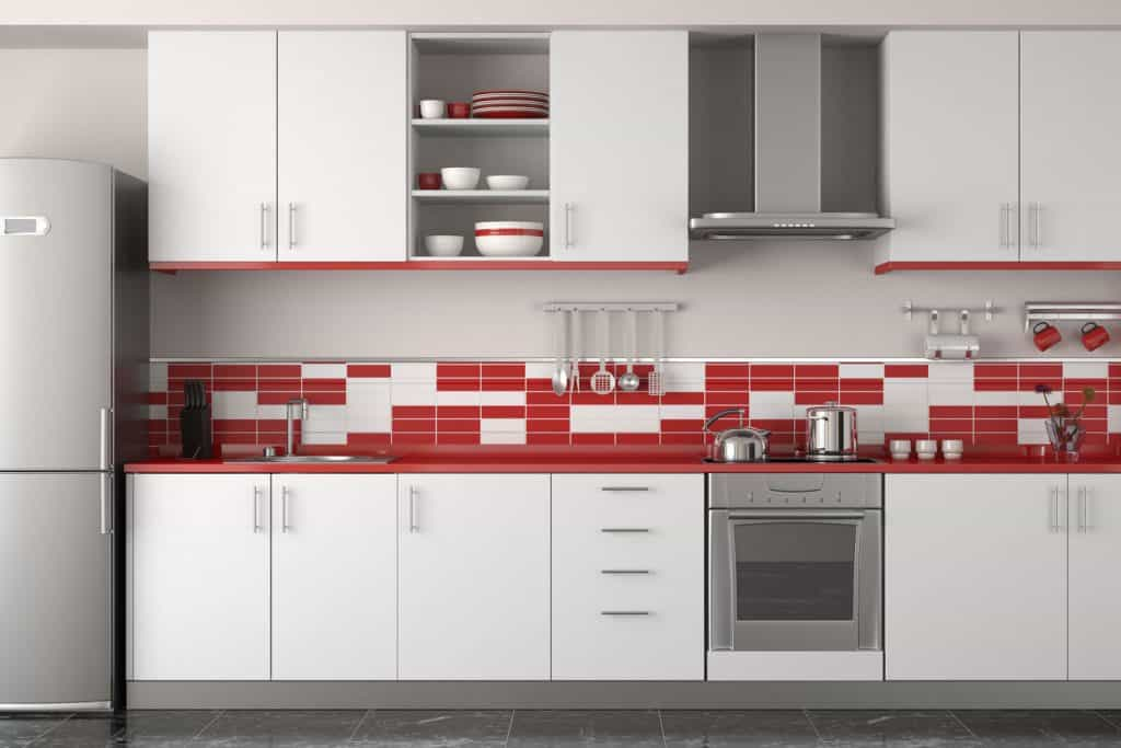 Interior of a modern contemporary kitchen with white paneled kitchen cabinetry with red and white tiled backsplash
