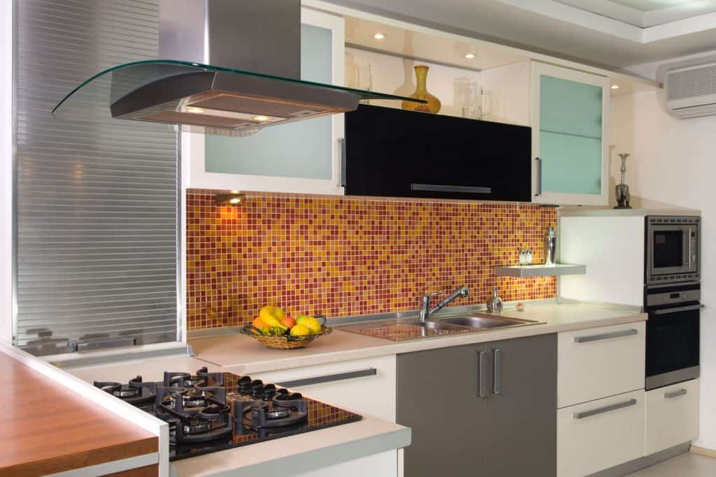 Interior of a modern kitchen with small square tiled decorative backsplash