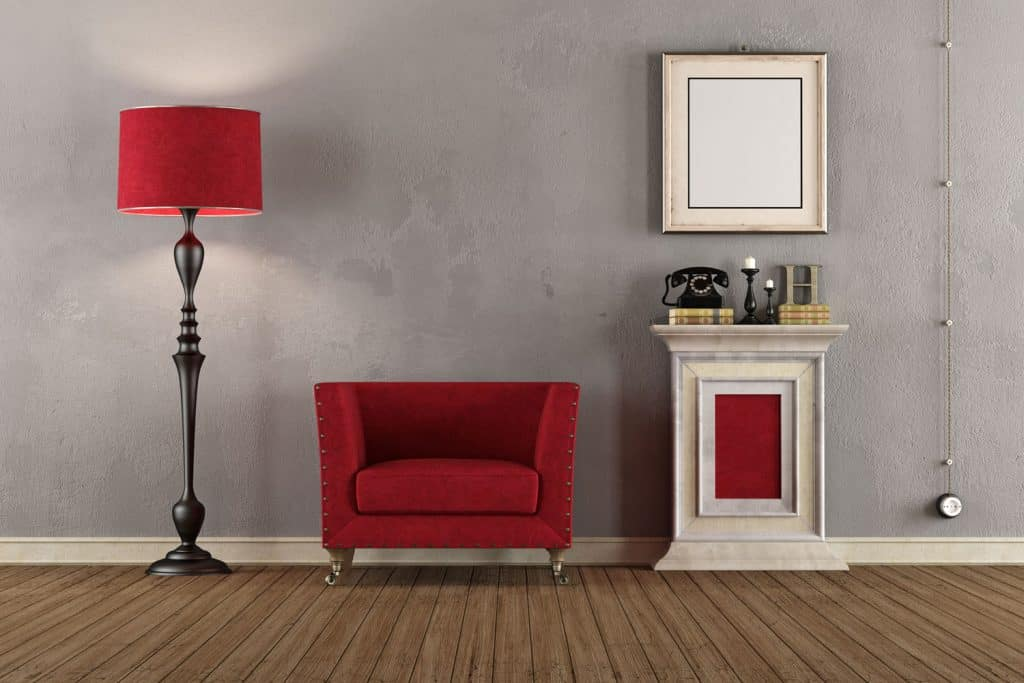 Interior of a modern living room with a gray wall, red chair, and a tall floor lamp on the side