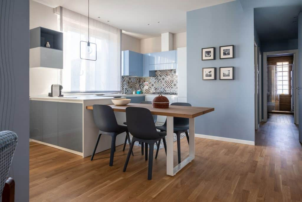 Interior of an ultra modern kitchen area with light blue painted walls and picture frames hanged on the wall