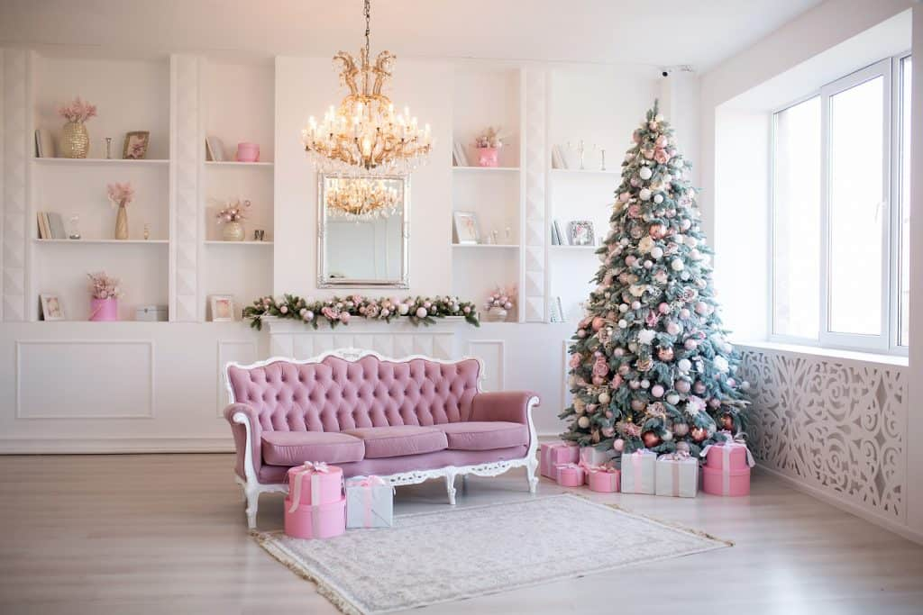 Interior of bright modern living room with fireplace and comfortable sofa decorated with Christmas tree and gifts.