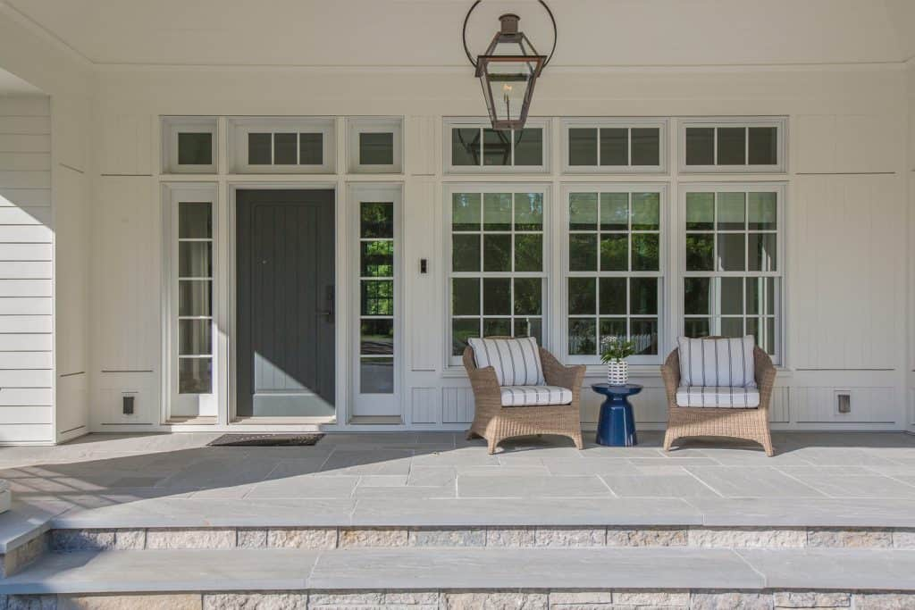 Lantern and chairs decorate this beautiful porch area with wide steps and lots of space