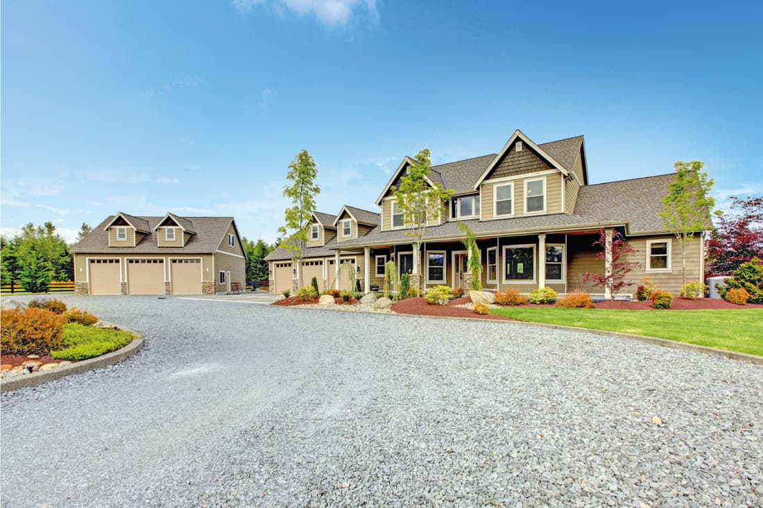 Large farm country house with gravel driveway and green landscape