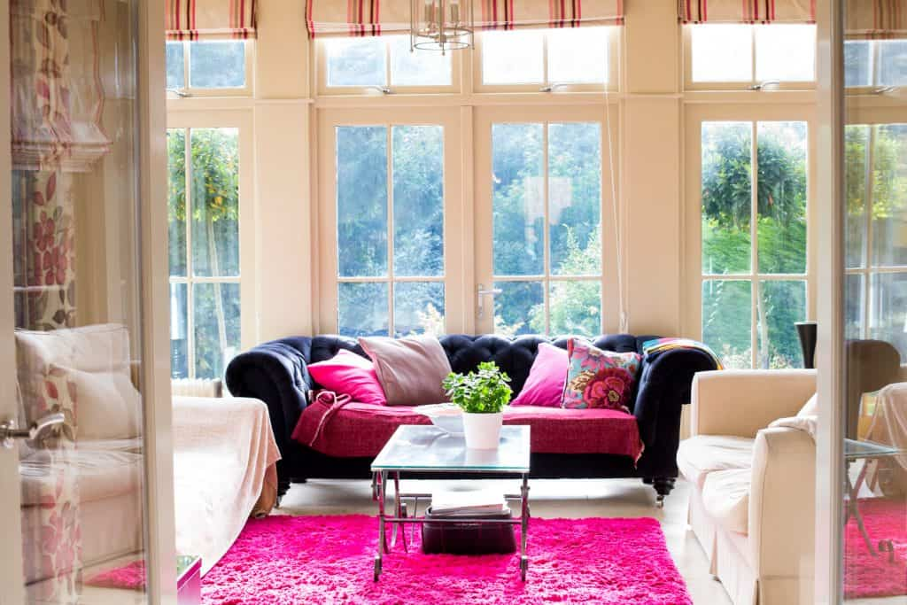 Large spacious living room, elegantly decorated with large windows looking onto a garden.