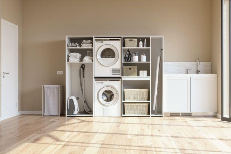Laundry Room With Beige Wall And Parquet Floor With Washing Machine, Dryer, Laundry Basket And Folded Towels In The Cabinet. Laminate floor. What Is The Best Flooring For A Laundry Room