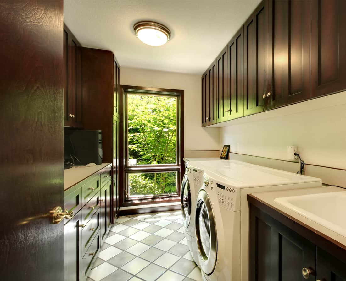 Laundry room with wood cabinets and upgraded checked tile