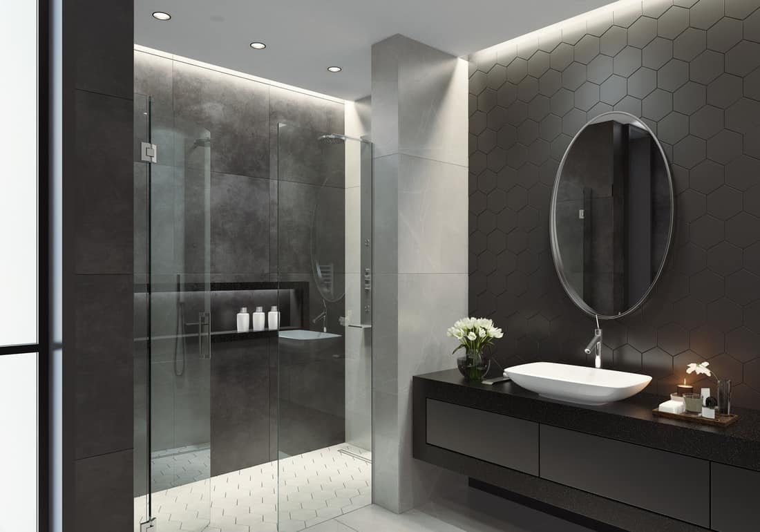 Luxurious bathroom with natural stone black and white tiles and hexagonal tiles. Long sink and big bath space. Candle lens flare. Oval and rounded mirror