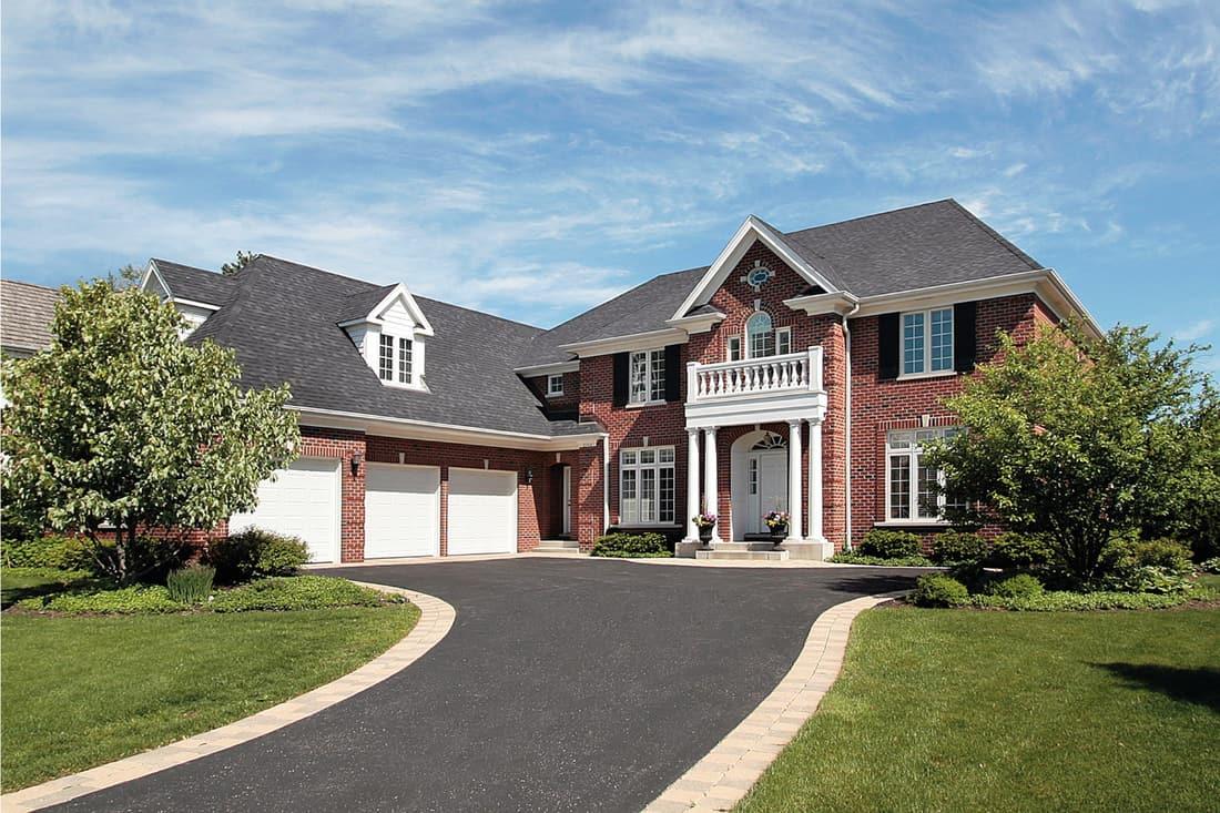 Luxury brick suburban home with nonporous tarmac driveway