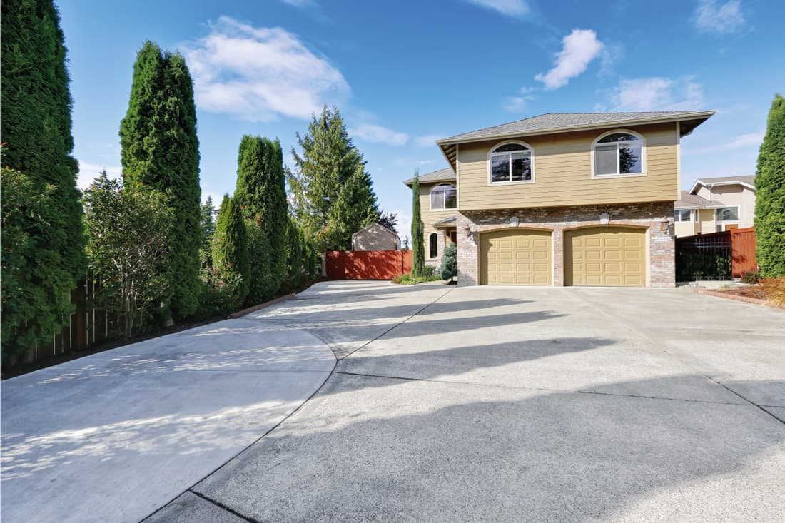 Luxury house in green exterior paint and large concrete driveway