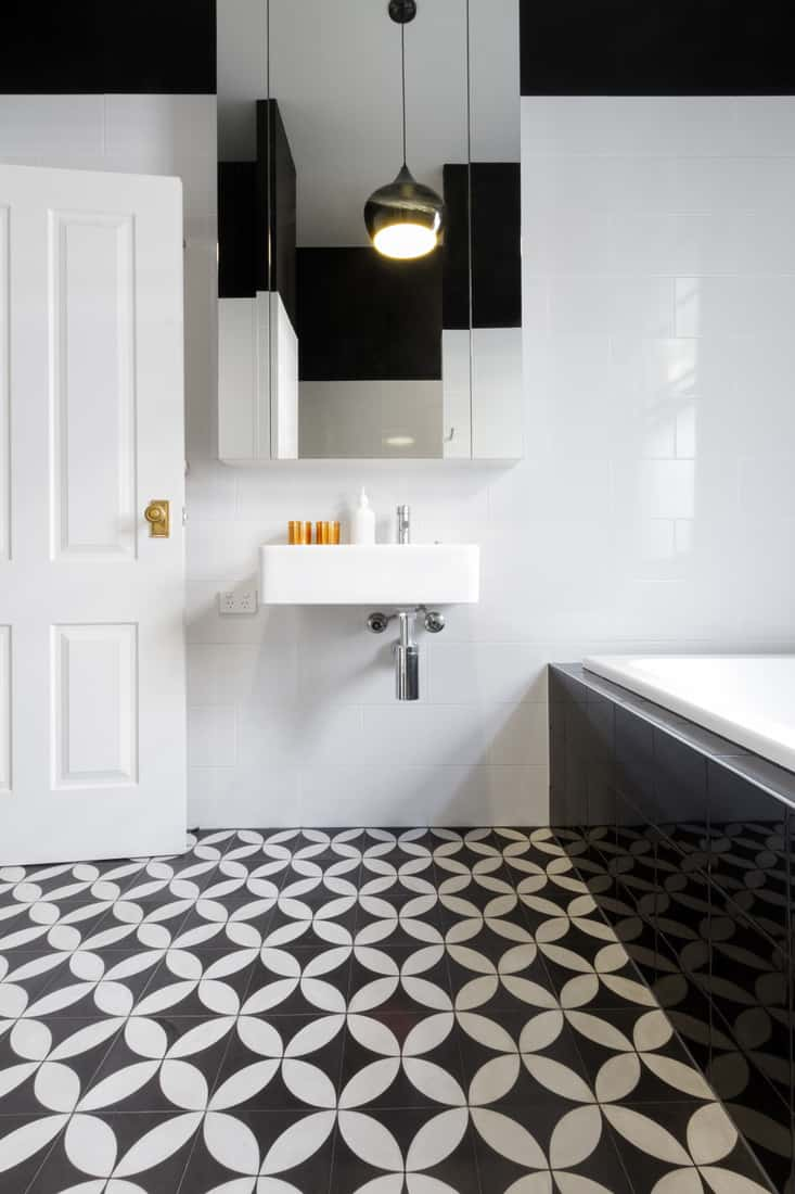 Luxury monochrome designer bathroom renovation with patterned floor tiles