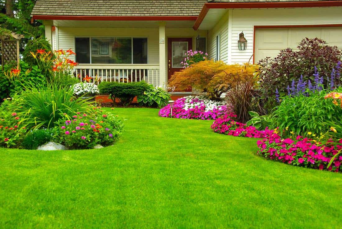 Manicured house and garden displaying annual and perennial gardens in full bloom