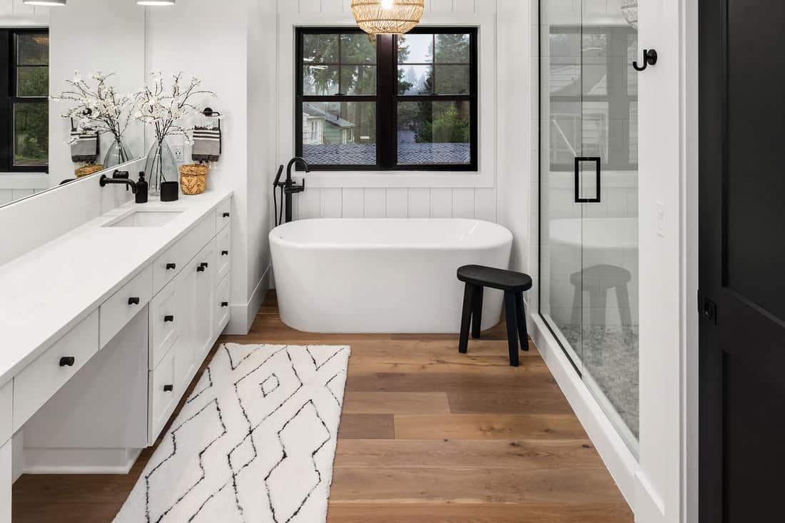 Master bathroom interior in new farmhouse style luxury home large mirror, shower, and bathtub, 7 Tips To Keeping A Bathroom Floor Dry After Showering
