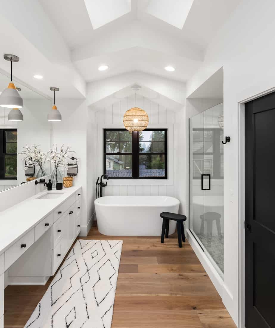 Master bathroom interior in new farmhouse style luxury home large mirror, shower, and bathtub