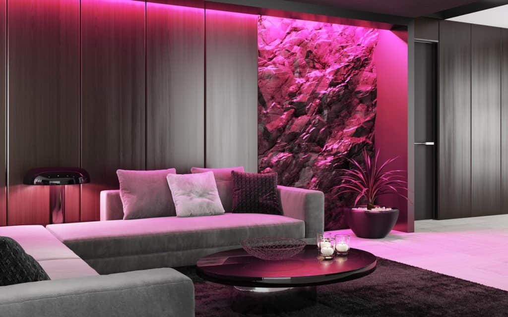 Modern RGB ambient lights concept like hue. Pink ambient light in modern matte black interior with mountain natural stone rock wall concept