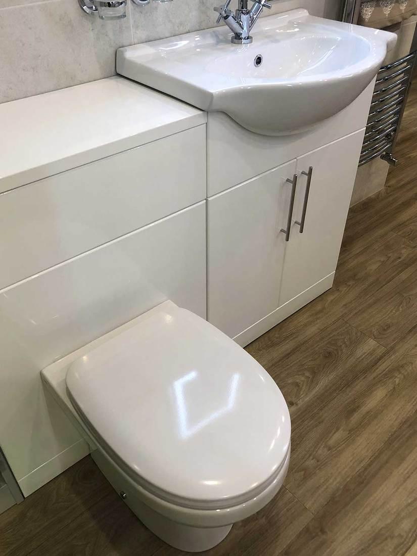 Modern bathroom suite with soft close toilet seat lid, vanity unit cabinet, and oak wooden laminate vinyl flooring floor