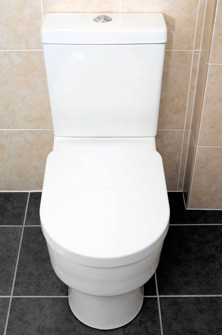 Modern close coupled toilet in tiled bathroom
