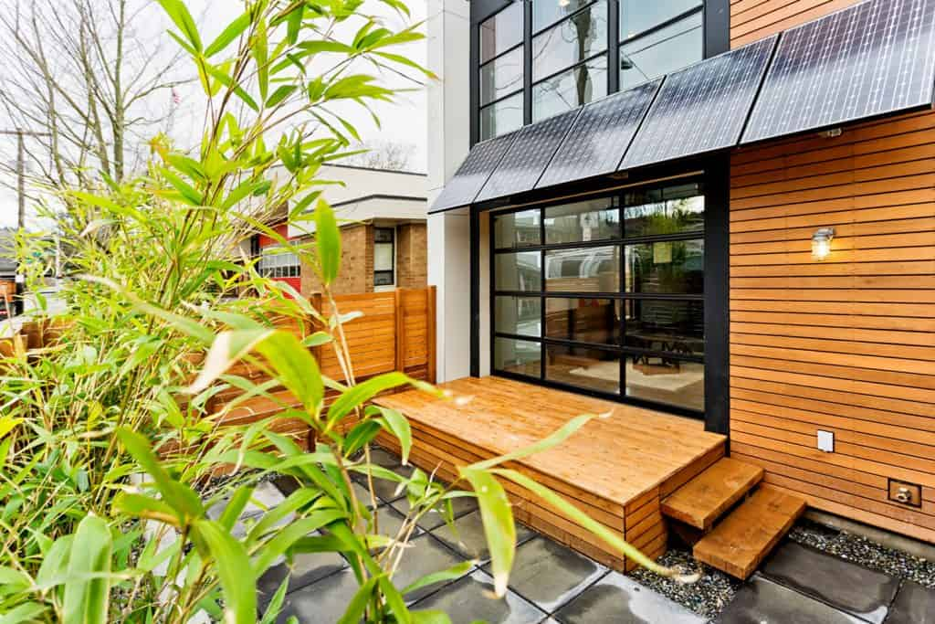 Modern contemporary house with wooden sidings and a small deck skirting area next to the huge windows