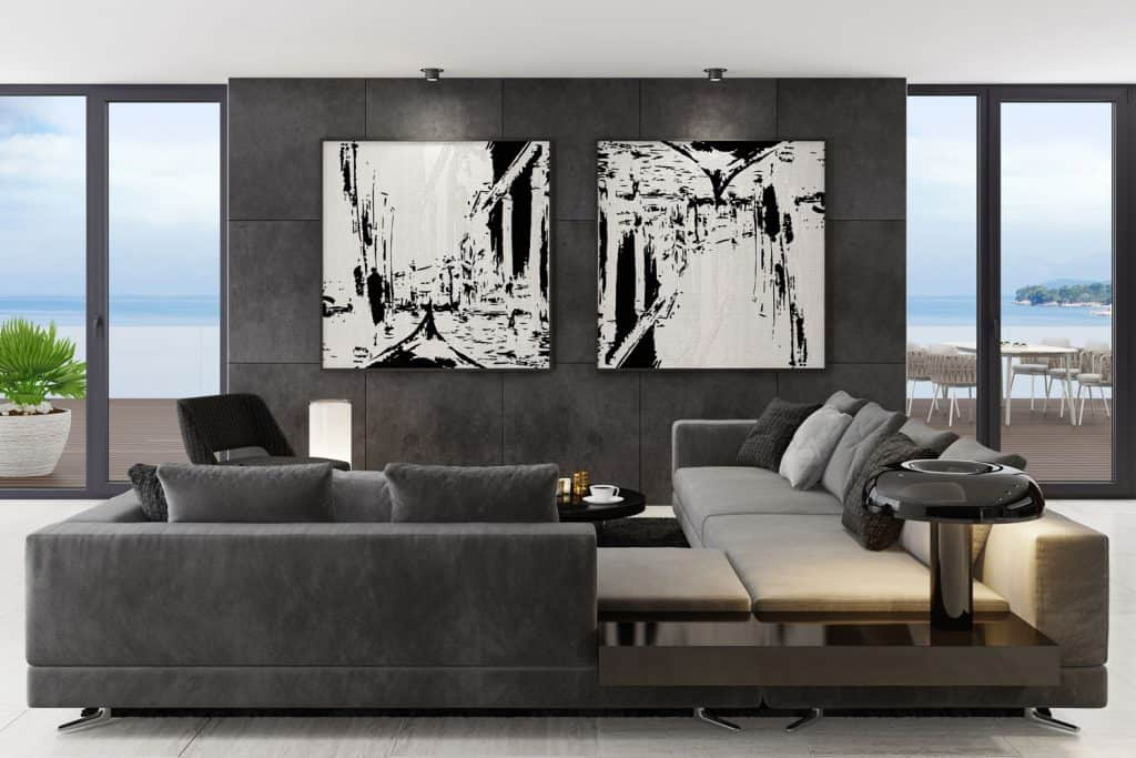 Modern contemporary living room with a gray sectional sofa with gray throw pillows and picture frames hanged on the wall