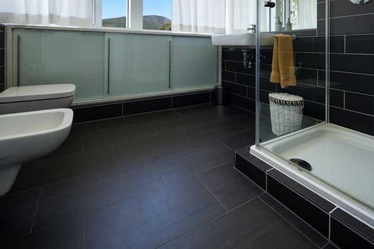 Modern house bathroom with glass shower and high ceiling, 15 Black Tile Bathroom Floor Ideas To Check Out