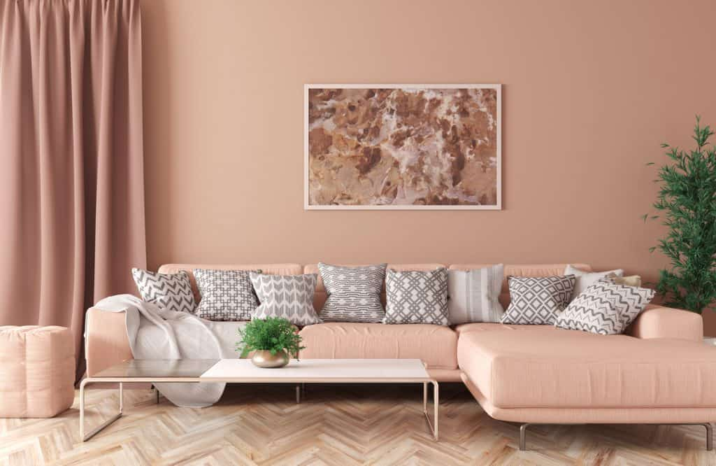 Modern interior of living room with peach corner sofa, coffee table