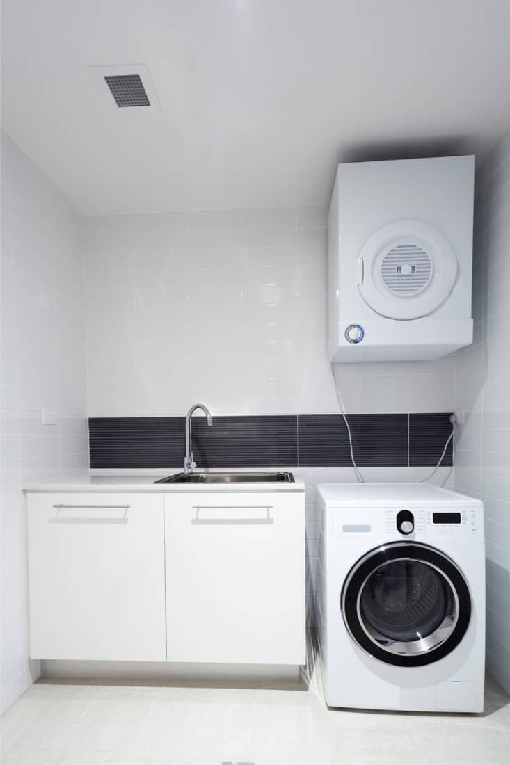Modern laundry room with white floor to ceiling tile, sink with cabinets, washer and dryer