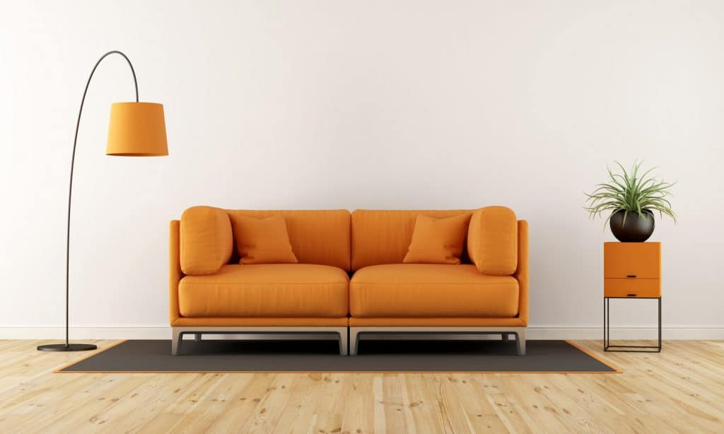 Modern living room with white wall, orange couch and floor lam