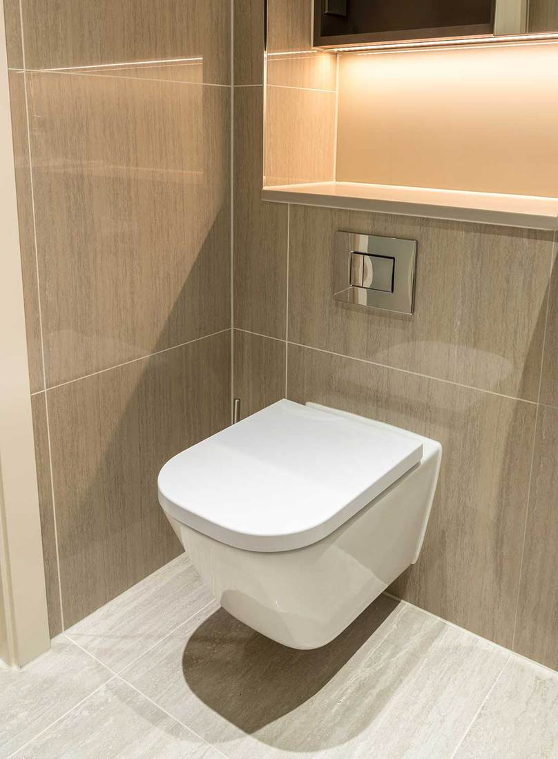 Modern toilet in clean apartment with white porcelain, tiled walls and floor