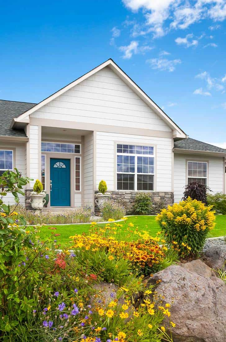 New home with gorgeous flower garden, peaked roof and blue sky