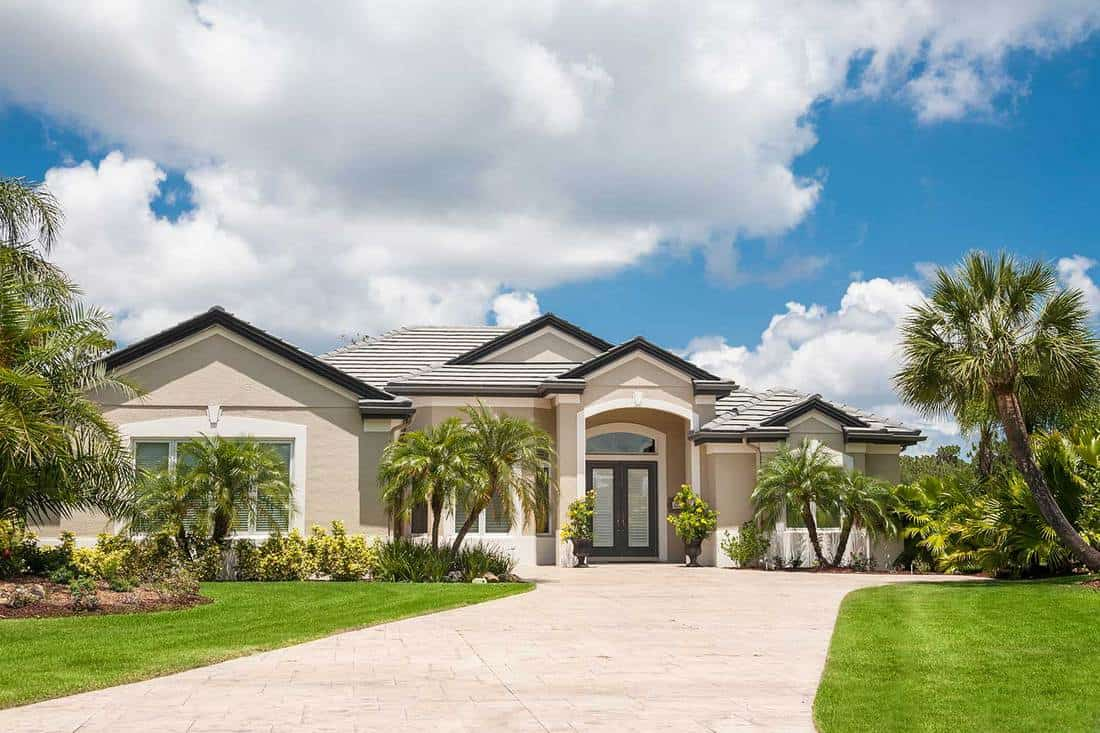 New luxury home in the tropics with driveway, palm trees, lush tropical foliage on front lawn