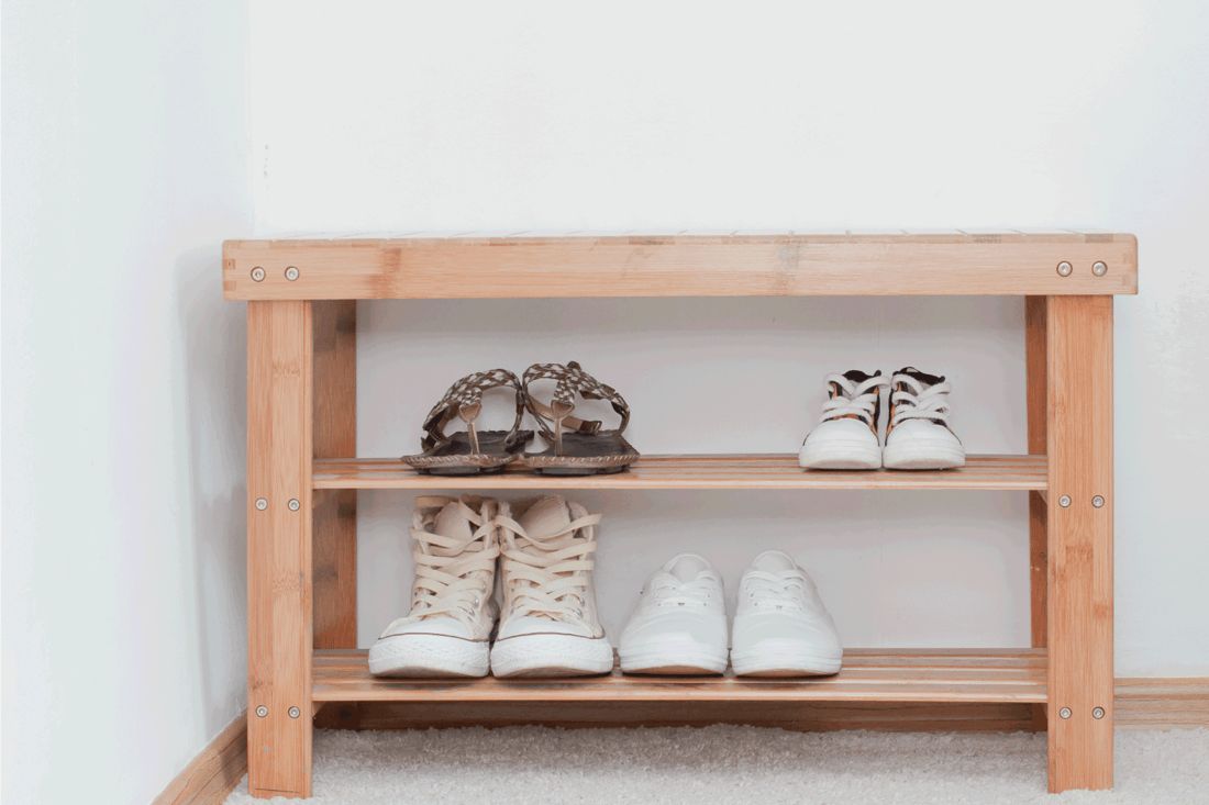 Old vintage wooden bench with shoes shelf, storage of shoes on the shelf