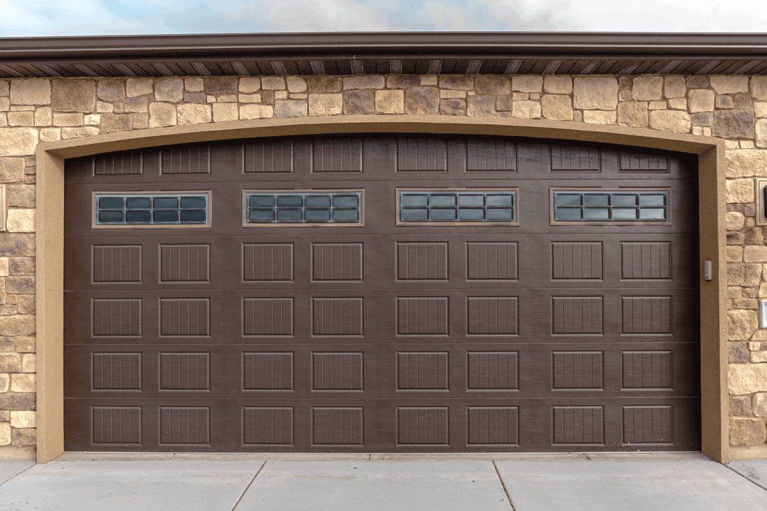 Panorama frame Large garage with double brown wooden door and decorative face brick walls with cement paved forecourt