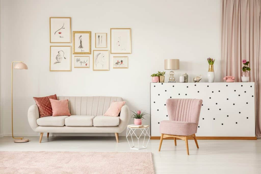 Pink chair next to table and sofa in living room interior with posters and gold lamp