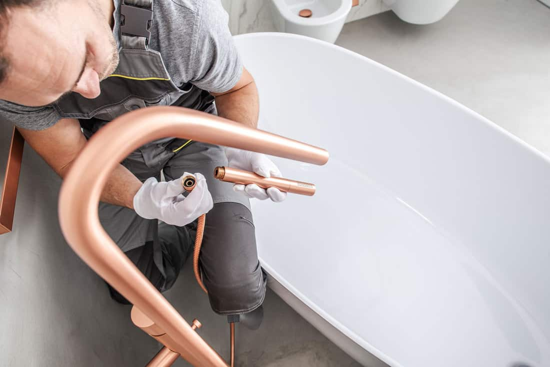 Plumber Connecting Pipes And Attaching Faucet Parts To Finish Installation Of Bathtub.