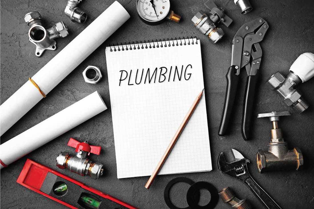 Plumbing concept. Notebook and plumber tools with blueprints on concrete structure