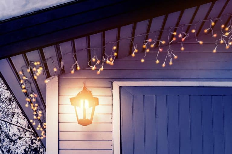 Porch of the house is decorated in the traditional Scandinavian style with a lantern and Christmas lights , How Can I Light My Porch Without Electricity? [A Complete Guide]