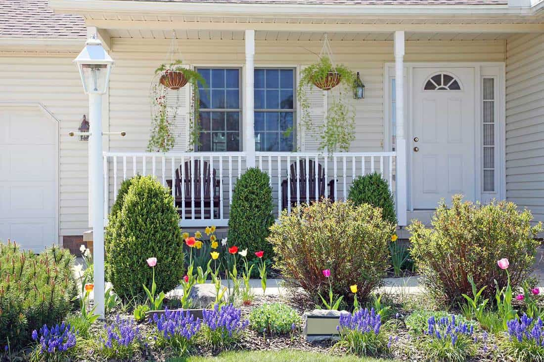 Pretty vinyl clad ranch home with Amish made chairs on the porch, and lovely spring landscaped yard